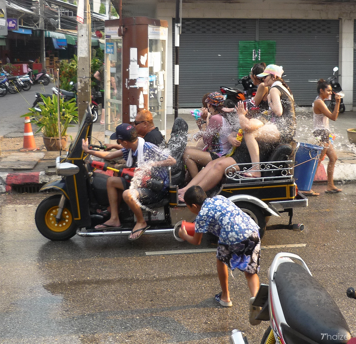 young lad throw water at convertible tuk-tuk in Chiang Mai